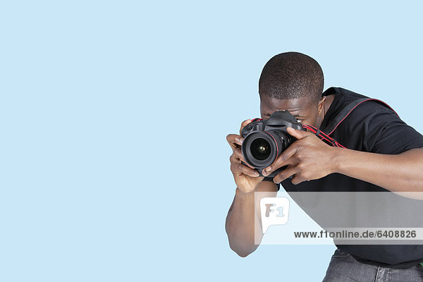 Mann  Fotografie  nehmen  über  Hintergrund  blau  jung  Fotoapparat  Kamera