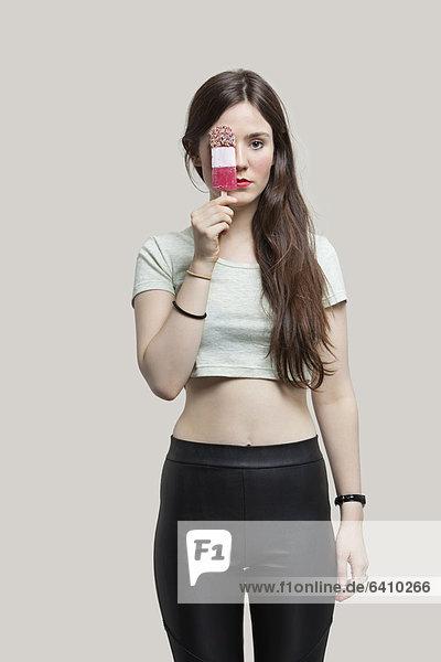 junge Frau junge Frauen Portrait Schönheit grau über halten Eis Hintergrund Sahne