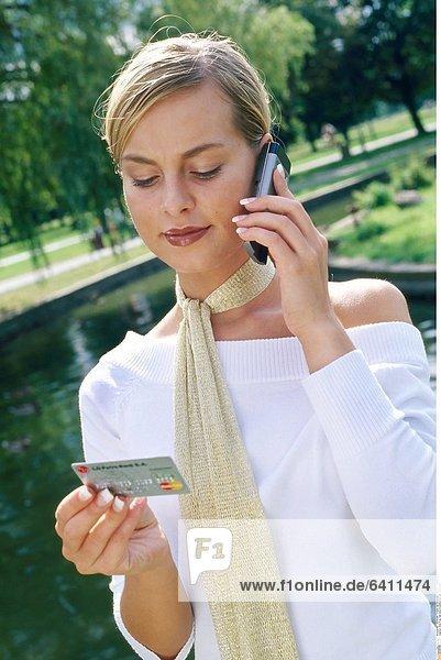 Eine Frau hält eine Kreditkarten und telefoniert
