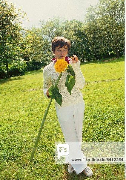 Frau mit Sonnenblume auf einer Wiese