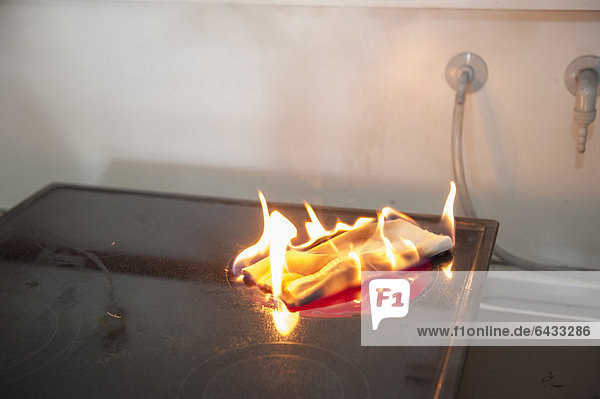 Towel lying on a switched on hot plate demonstrating fire causes such as kitchen fires  Stuttgart  Baden-Wuerttemberg  Germany  Europe