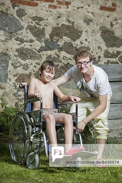 Junge im Rollstuhl mit Begleiter