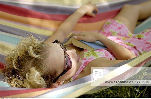 Junge Frau schläft in Hängematte