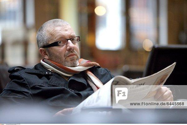 Mann liest Zeitung in einem Cafe