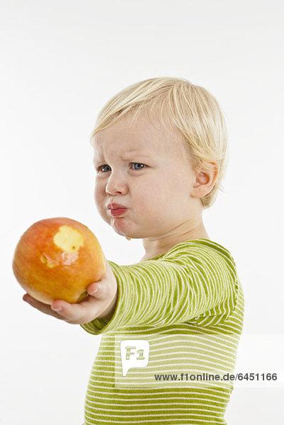 Ein Kleinkind  das ein Gesicht macht  während es einen Apfel hält.