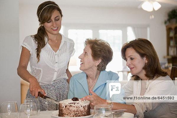 Eine junge Frau serviert Kuchen für ihre Mutter und Großmutter.
