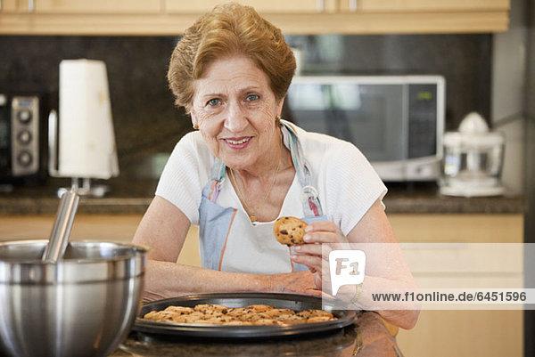 Eine ältere Frau mit frisch gebackenen Keksen Eine ältere Frau mit frisch gebackenen Keksen