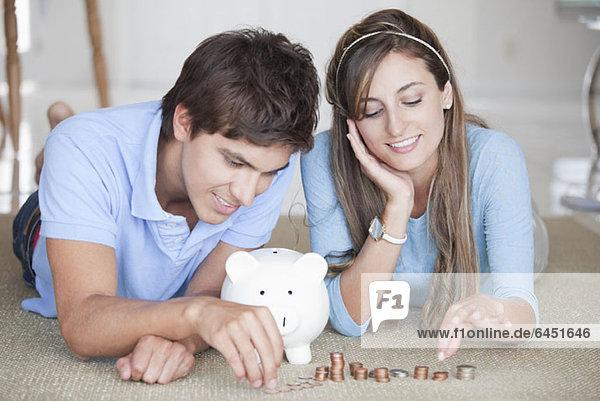 Ein junges  fröhliches Paar  das Münzen auf dem Boden zählt.