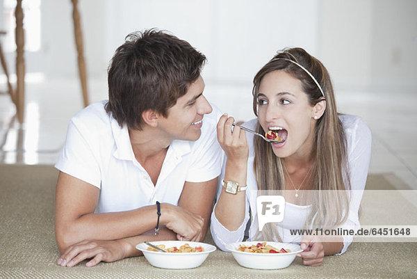 Ein junges Paar liegt auf dem Boden und isst Müsli zum Frühstück.