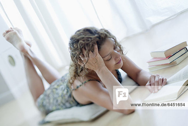 Eine Frau  die auf dem Boden liegt und ein Buch liest.
