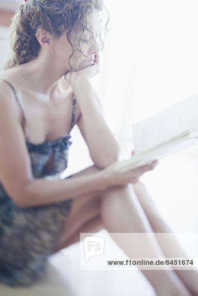 Eine Frau sitzt auf dem Boden und liest ein Buch.