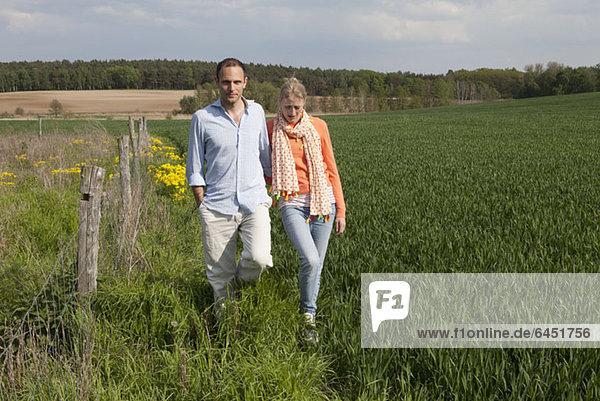 Ein Paar  das nebeneinander auf einem Feld spazieren geht.