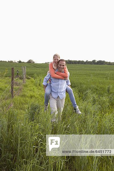 Ein Mann  der seiner Freundin eine Huckepackfahrt durch ein Feld macht.