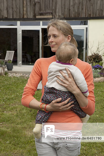 A woman holding her baby in her backyard