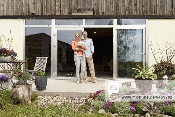 Ein Mann und eine Frau halten ein Baby auf der Terrasse vor ihrem Haus.