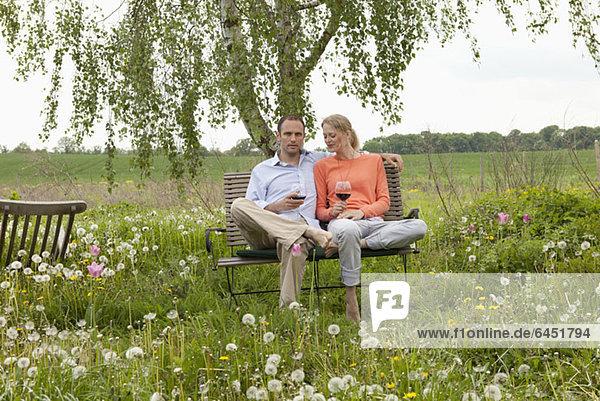 Ein Paar sitzt auf einer Bank im Garten und genießt ein Glas Rotwein.