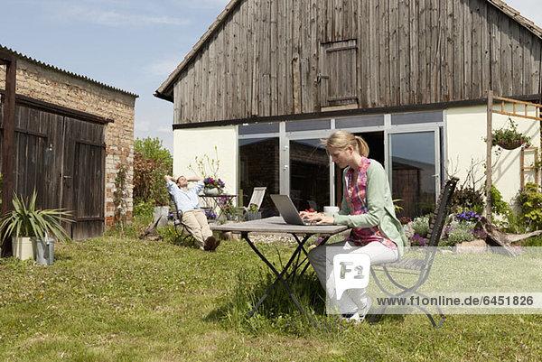 Eine Frau  die einen Laptop benutzt und in ihrem Garten frühstückt.