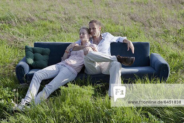 Ein Paar  das auf einem Sofa in einem Grasfeld sitzt.