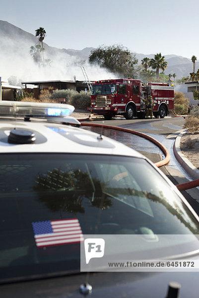 Ein Polizeiauto und ein Feuerwehrauto am Tatort eines brennenden Hauses in einem Vorort