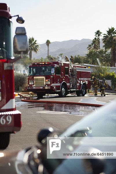 Ein Feuerwehrauto und Feuerwehrleute auf einer Vorstadtstraße neben einem brennenden Haus.