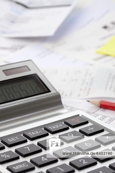 Ein Taschenrechner über einem Durcheinander von Finanzunterlagen