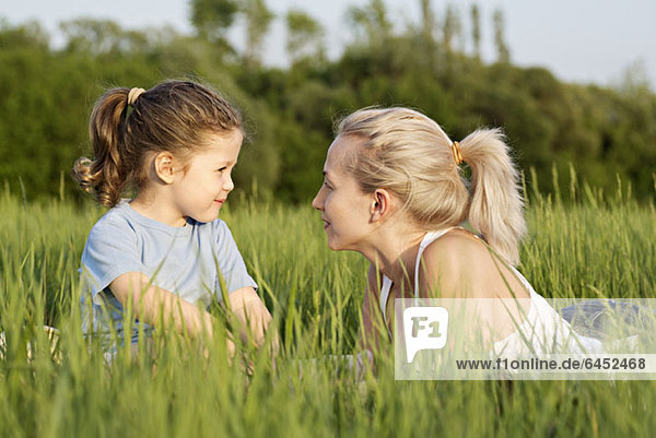 A young girl and a woman relaxing in a field together