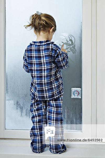 Ein Mädchen im Pyjama und mit Kondensation auf Glas.