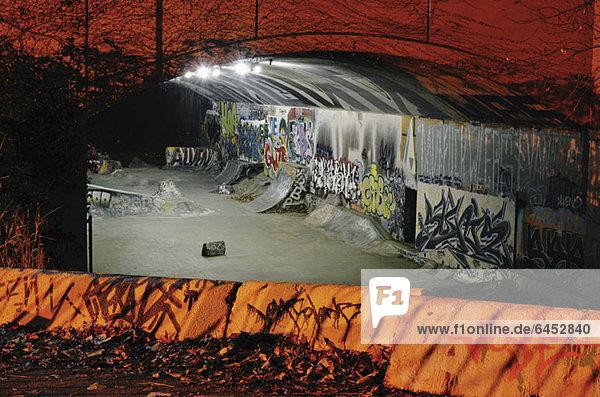 Skateboard-Rampen und Graffiti im Tunnel bei Nacht Skateboard-Rampen und Graffiti im Tunnel bei Nacht
