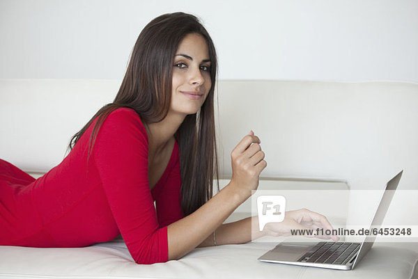 Woman in red on sofa with laptop