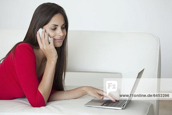 Frau in Rot mit Telefon und Laptop