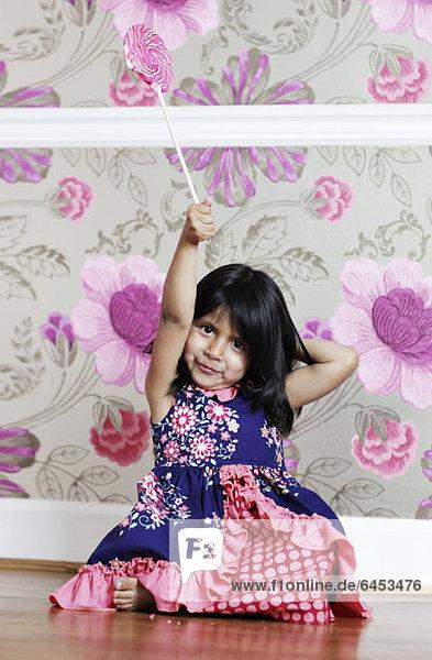 Ein junges Mädchen hält einen Lolli in der Luft.