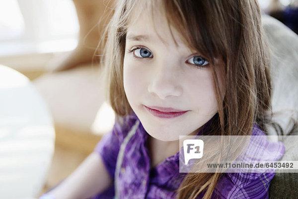 Ein junges Mädchen schaut gelassen in die Kamera.