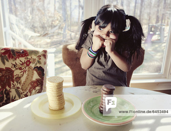 Ein Mädchen  das versucht  sich zwischen zwei Stapeln Vanille- und Schokokeksen zu entscheiden.