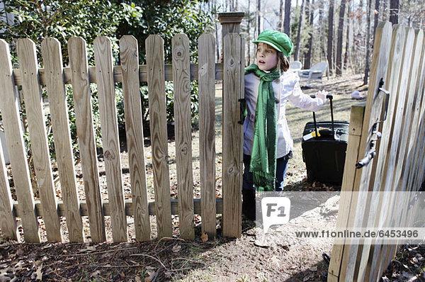 Ein Mädchen  das ängstlich am Zaun zu ihrem Hof wartet  mit einem Koffer