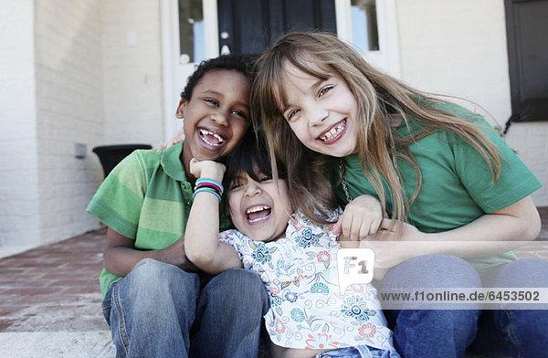 Drei Kinder  die liebevoll lachen  während sie auf der Vordertreppe sitzen.