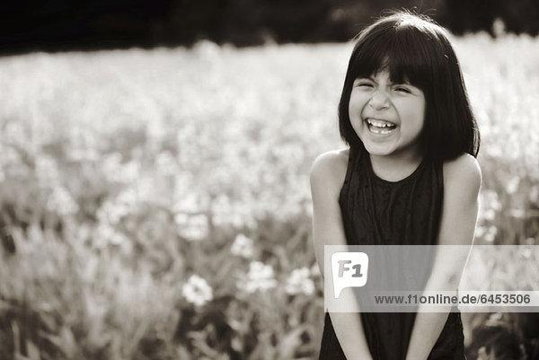 Ein junges Mädchen auf einem Feld  das im Sonnenlicht lacht.