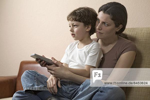 Ein Junge sitzt auf dem Schoß seiner Mutter und sieht fern.