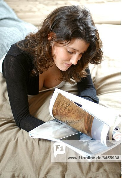 Junge Frau liest Magazin