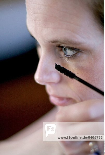 Frau trägt Mascara auf *** Local Caption ***