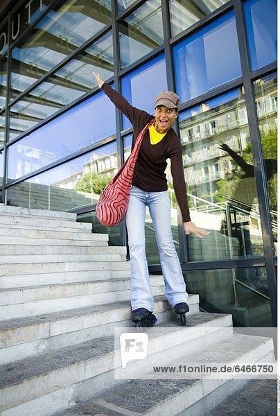 Junge Frau mit Rollerskates auf einer Treppe