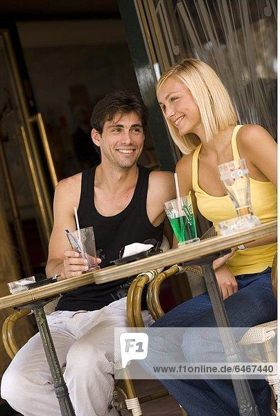 Junges Paar sitzt in einem Straßencafé *** Local Caption ***