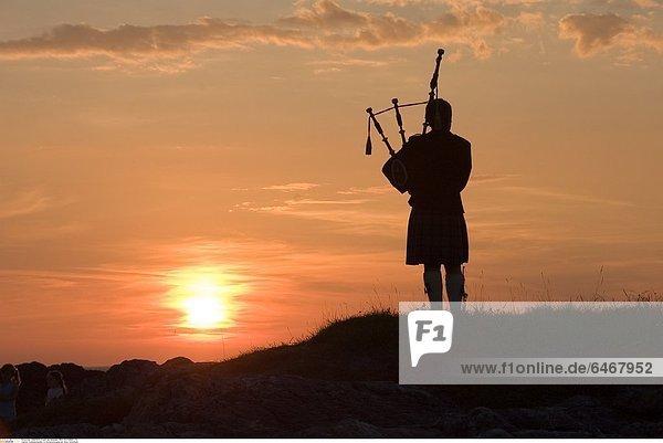 Dudelsackspieler im Sonnenuntergang auf Skye  Schottland