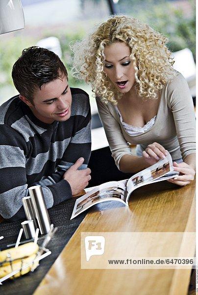 Paar blättert gemeinsam in einem Magazin