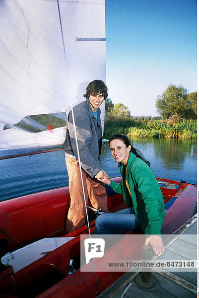 1216671 outdoor day summer couple young man woman girl boy brunette dark haired 20-25 stand sit water lake blouse blouses green grey sailing boat red vacation holidays recreation hold hand hands help get out moor smile smiling vertical
