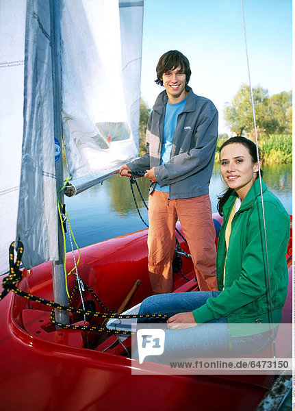 1216673 outdoor day summer couple young man woman girl boy brunette dark haired 20-25 stand sit water lake blouse blouses green grey sailing boat red vacation holidays recreation hold hawser cordage set sail smile smiling close up vertical
