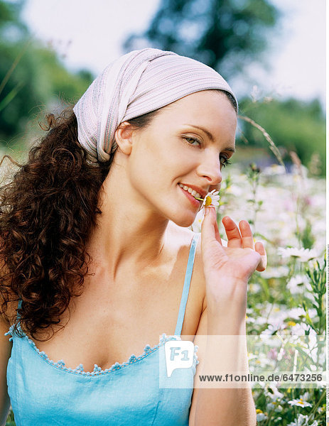 1222613 outdoor day summer meadow field flower flowers camomile camomiles young woman brunette headscarf white 25-30 rest relax vacation holidays dress blue sit herb herbal medicine cosmetics natural medicine alternative care portrait close up smile smiling eat people vertical