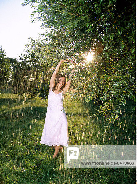 1222901 outdoor park garden day summer young woman girl 20-25 brunette dress white people jump foot feet barefoot smile smiling water rain raindrop raindrops raining rest relax stand vertical long hair