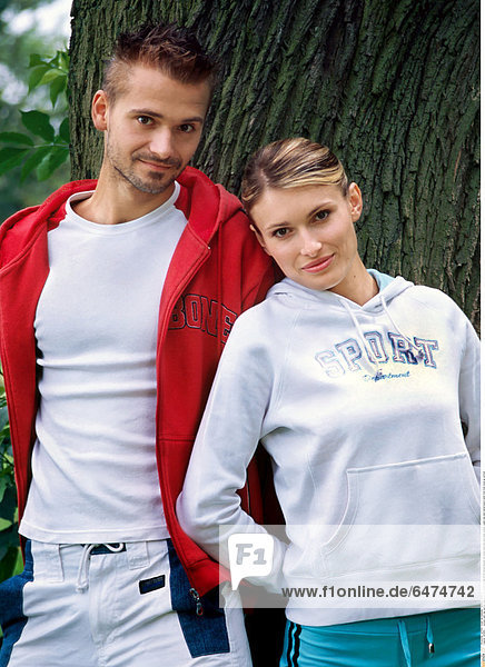1222683 outdoor park day summer young woman people blonde 25-30 blouse blouses red white track suit suits smile smiling couple man dark haired beard resist tree trunk close up vertical