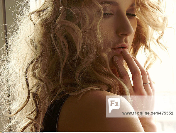 1224779 indoor flat bedroom people woman young 20-25 blonde long hair portrait close up think dream sad sadness ring jewellery horizontal