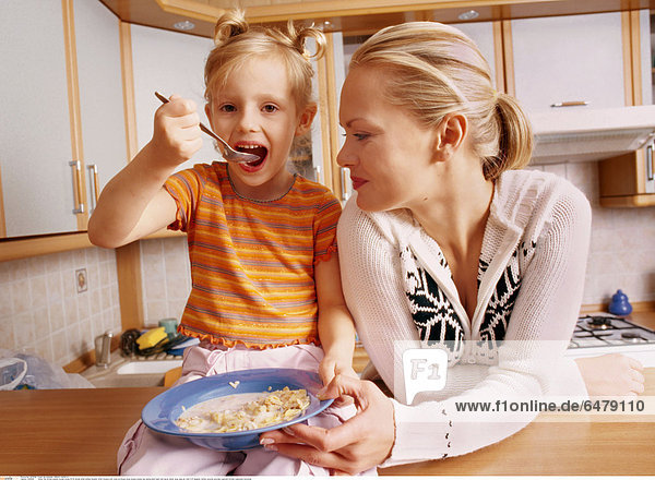 1228505 indoor flat kitchen people woman young 25-30 blonde smile smiling sweater white trousers pink close up blouse stripe stripes striped eat eating plate basin hold spoon dinner soup meal girl child 5-10 daughter mother ponytail ponytails cupboard kitchen cupboards horizontal